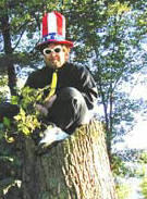 Donnie Love sitting on a tree stump wearing a big tall Uncle Sam hat